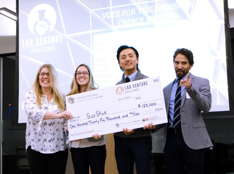 The SickStick team poses with a check for 25,000 after a big win in a competition called the Lab Venture Challenge.