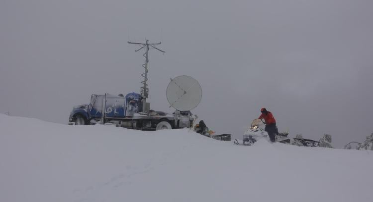 A man rides a snowmobile next to a radar dish mounted on the back of a truck.