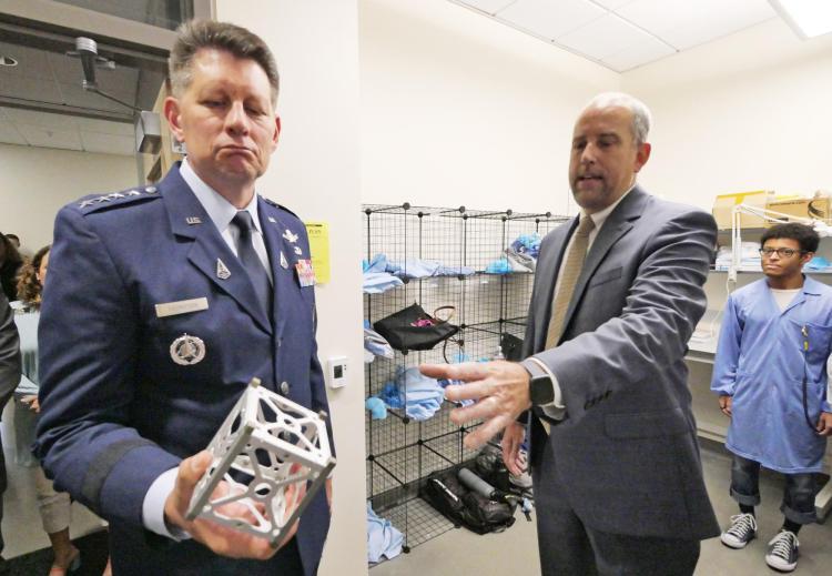 Scott Palo hands Gen. Thompson the frame for a CubeSat