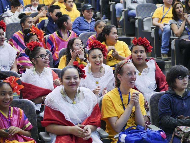 Students donning traditional Spanish dress, sit in auditorium