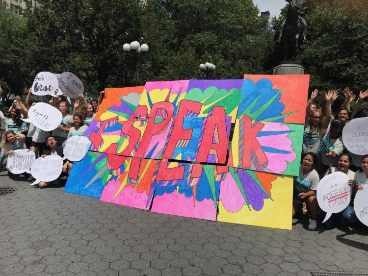 Girls hold signs saying 'Speak,' an example of an 'Ethical Spectacle'