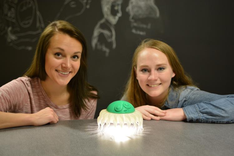 Ariel Wiggan and Sarah Wachter  squat behind a gray table with their chest and head above it. Between them is their invention, Tentacles of Light, a lamp which resembles a squid, which has  a green head with a face on top and white legs that hang down.