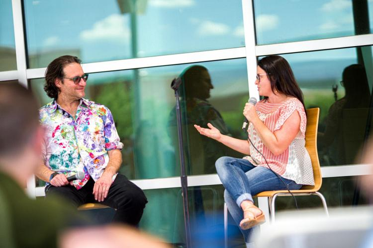 Delnaey Keating speaks into a microphone on an outdoor stage with Brad Feld
