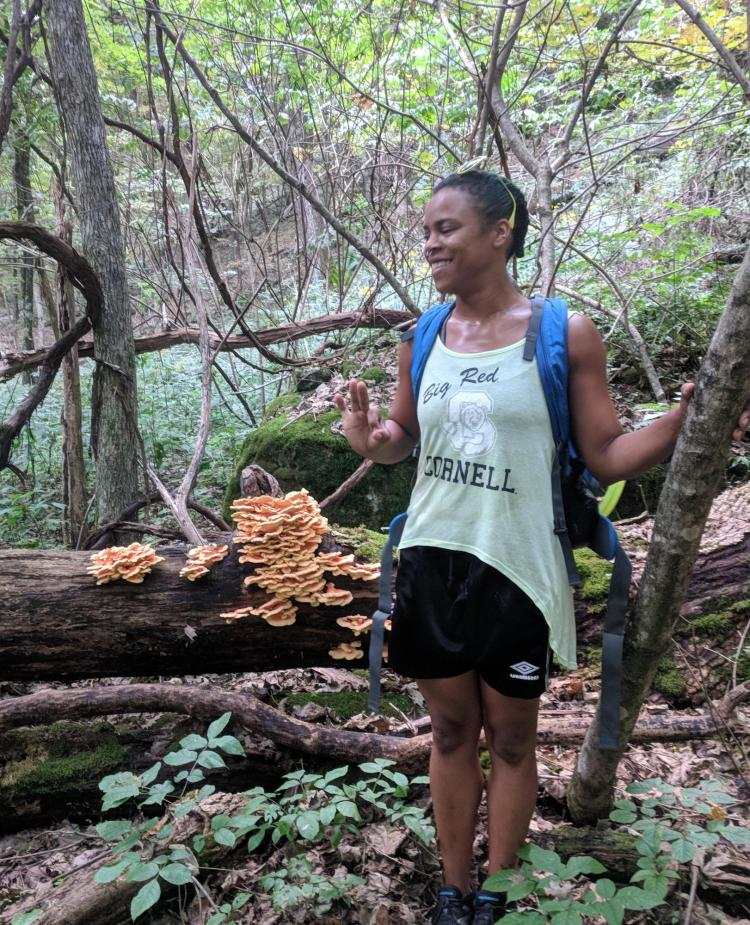 Shaz Zamore poses next to mushrooms growing on a log.