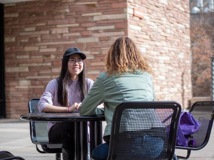 Zhen Qu talks with another student on campus