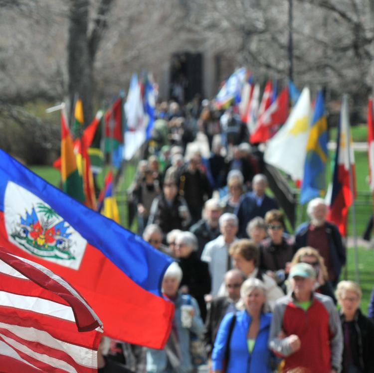 People walking between a row of flags during the Conference on World Affairs