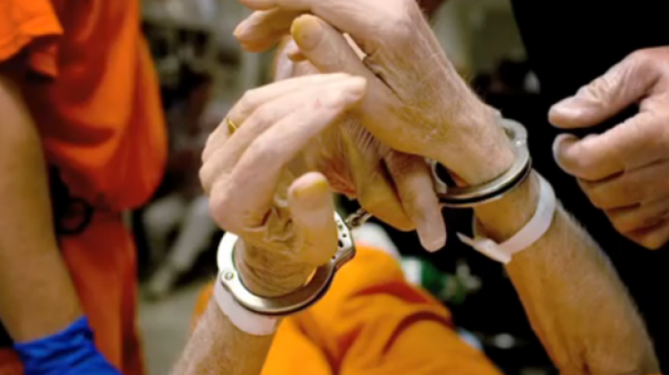 Arms of elderly person in handcuffs