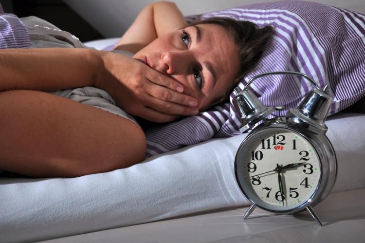 woman laying awake in bed next to alarm clock