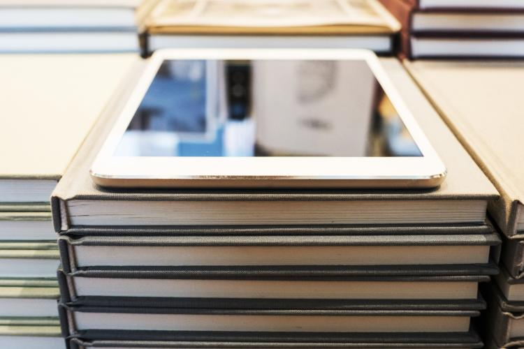 A modern digital tablet sits atop stacks of books.