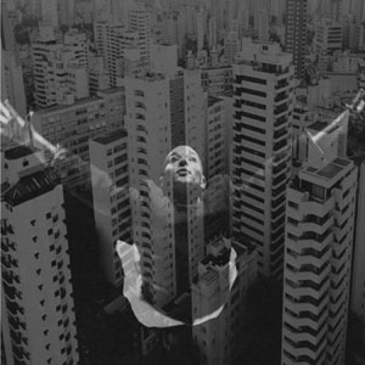 An image of a woman is superimposed in black and white over skyscrapers