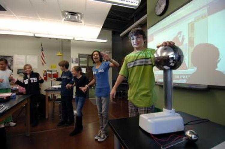 "From right to left, sixth-graders Gerald Robinson, Carmen Houck, Gemma Truesdell, Wes Dolsen, Ellie Megerle and Livia Diener of Southern Hills Middle School in Boulder experiment with static electricity using a Van de Graaff generator and the ""John Travoltage"" PhET Interactive Simulation. (Photo by Patrick Campbell/University of Colorado)"