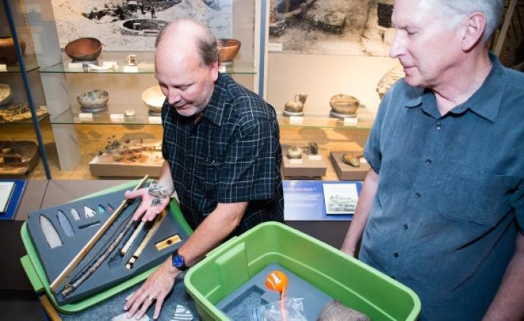 Senior museum educator Jim Hakala, left, and anthropology curator Steve Lekson prepare a fossil kit to be delivered to a Colorado classroom.