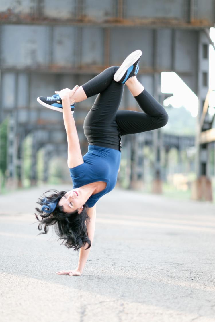 A woman break dances, standing on one hand