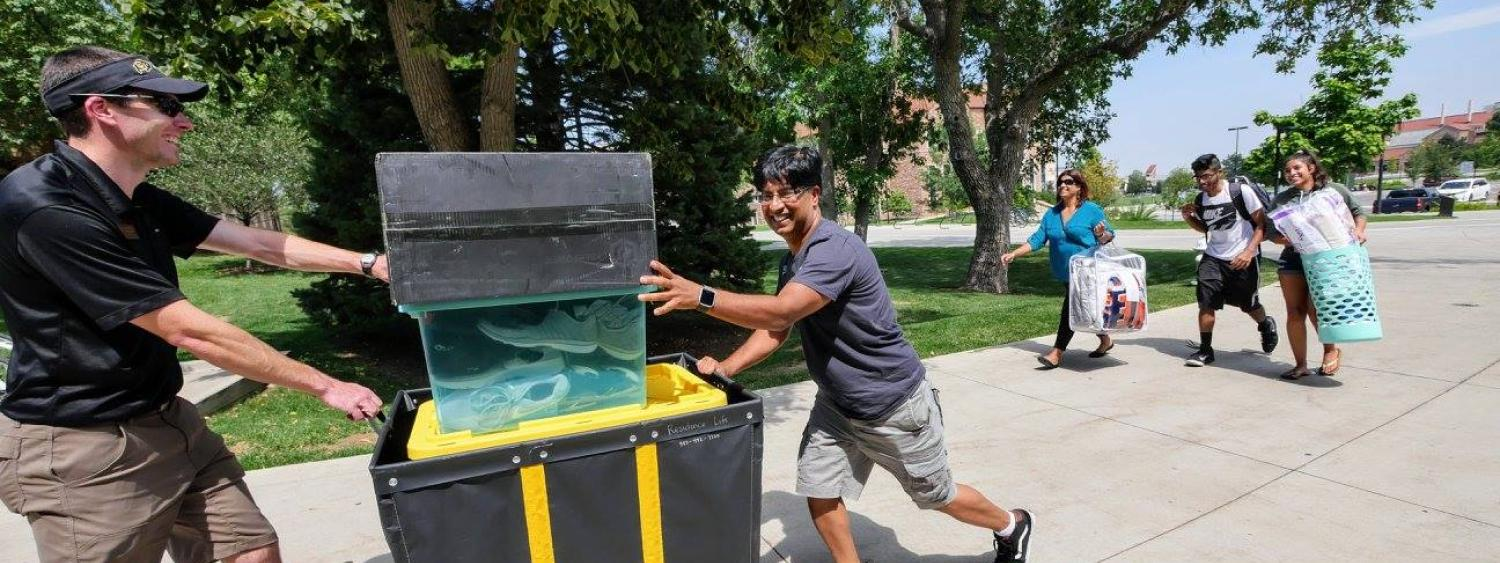 Som Aryal pushes a moving cart to help his son,Sohan Aryal, a freshman mechanical engineering major from Aurora, right, move in to Hallett Hall. Sohan also got help moving from his sister, Suhani, and mother Merina and volunteer David Schofield. (Photo by Glenn Asakawa/University of Colorado)