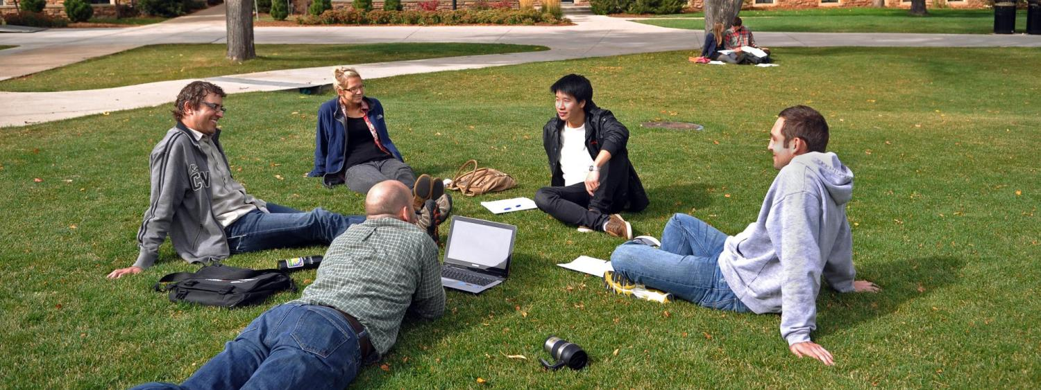 People sit in a circle on a campus lawn.