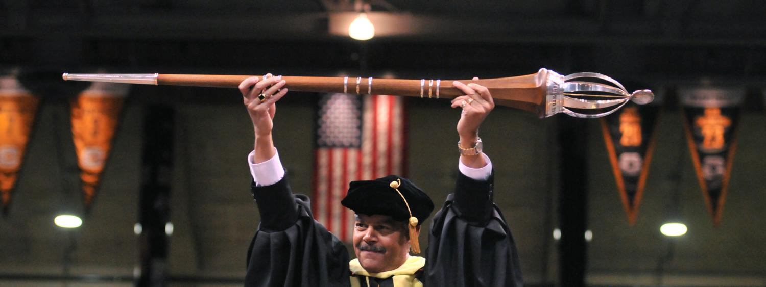 Jim Williams holds the university mace, or staff, during a commencement ceremony.