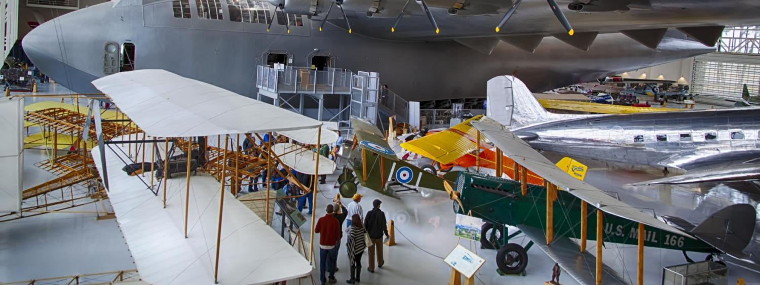 Visitors look at planes at the Wings Over the Rockies Air and Space Museum