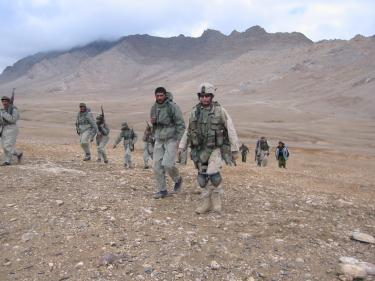 Mitch Utterback along with several other members of armed forces walk in what appears to be a dry climate, out in open space with mountains in the background.
