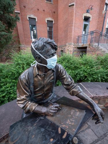 Robert Frost sculpture wearing a mask