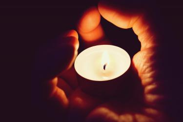 Person holds votive candle in hand