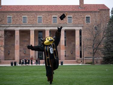 Chip tossing a graduation cap.