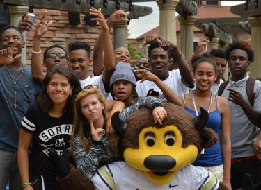 A group of students poses with Chip during the boys2MEN Leadership Summit