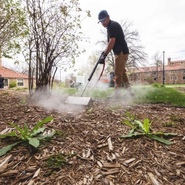 Grounds technician Pedro Vasquez uses a machine that provides hot steam to safely kill weeds