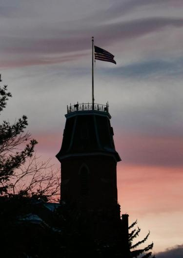 Silhouette of Old Main with sunset in background