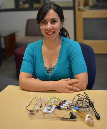 Fuji Robledo, dressed in a light blue shirt with her arms crossed,  sits in front of a desk that shows the portable water monitoring system she developed. The device is about the size of a large book and has wires and probes coming out of a clear board.