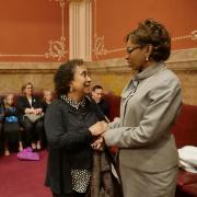 Professor Polly McClean, left, speaks with State Senator Rhonda Fields.