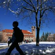 Student walks past Norlin Library in the snow
