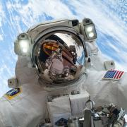 An astronaut is pictured in outer space with Earth in the background.