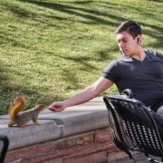 Senior Alex Elnagdy shares a peanut with a squirrel on campus. Photo by Glenn Asakawa.