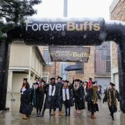 Graduates pose for photo under Forever Buffs blow-up arch