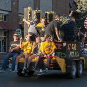 Students ride on a Homecoming float and wave to the crowd