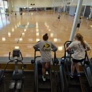 Students run on ellipticals while overlooking the basketball courts