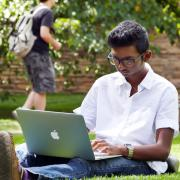Student working on laptop, sitting in grass on campus