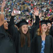 Girl raises hands in excitement during commencement