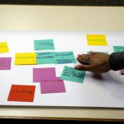 Campus community member adds sticky note to board during Diversity and Inclusion Summit
