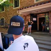 Man wearing black Fall Welcome Squad hat