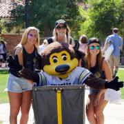 Three students strike a pose with Chip.