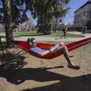 Student lounging in hammock reading on campus
