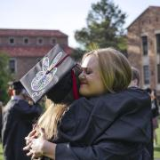 Two graduating Buffs share a hug