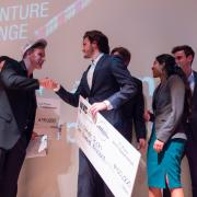Stride Tech founders on stage at Boulder theater after winning the New Venture Challenge.