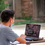 student joins virtual event on laptop outside
