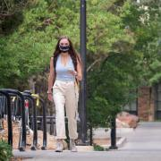 Student walking on campus while wearing a mask