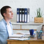 Man rubs back while sitting at desk