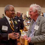 Awardee Olester Benson (left) converses with another person at the 2018 Alumni Awards ceremony.