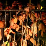 Horde of zombies attempts to break through metal gate