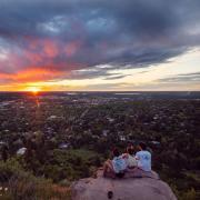 three friends watch the sunrise at Flagstaff